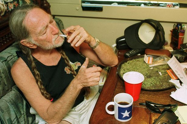 Willie-Nelson-takes-a-drag-off-a-joint-while-relaxing-at-his-home-in-Texas-2000s-1861533.png